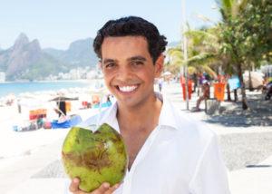 Junger Brasilianer mit Kokosnuss am Strand